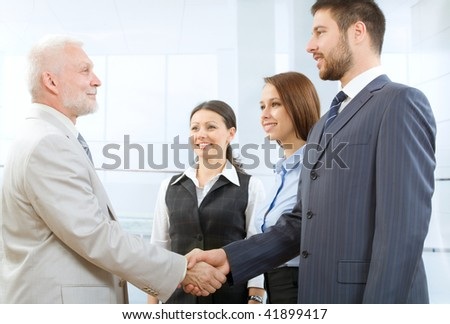 Business people shaking hands in a modern office centre - stock photo