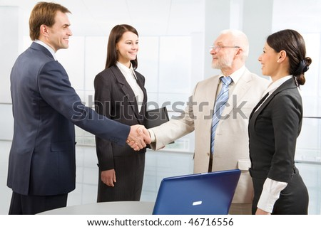 Business people shaking hands in an office - stock photo
