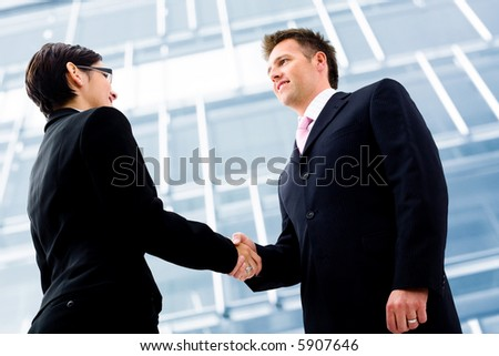 Business people shaking hands in front of an office building. Selective focus is placed on the hands. - stock photo