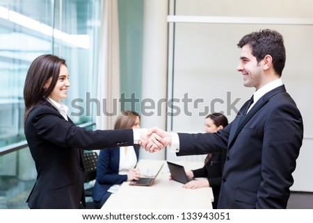 Business people shaking hands in the office, finishing a meeting - stock photo