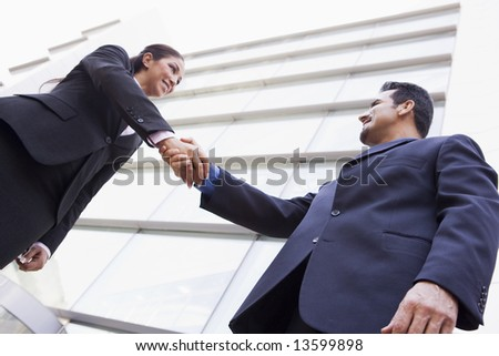 Business people shaking hands outside modern office - stock photo