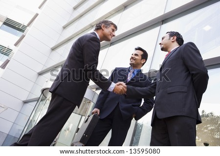 Business people shaking hands outside modern office building - stock photo