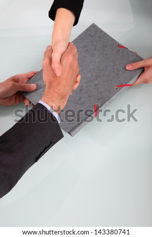 Business people shaking hands over a folder - stock photo
