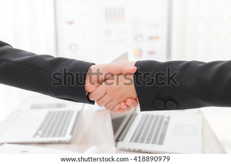 Business people shaking hands over laptop