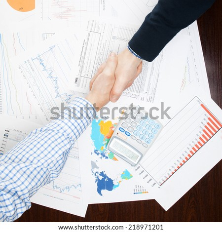 Business people shaking hands over table - view from top - 1 to 1 ratio - stock photo