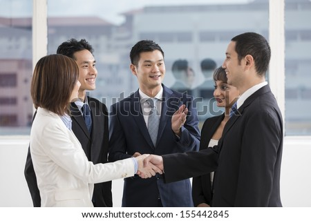 business people shaking hands with a team of colleagues around them - stock photo