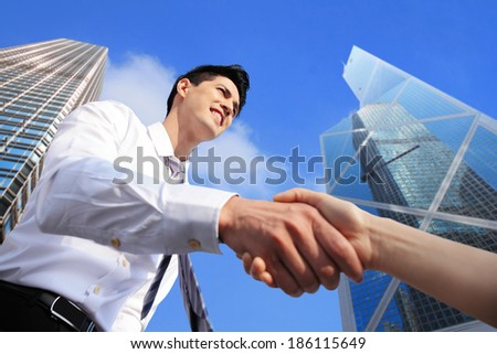 business people shaking hands with city background - stock photo
