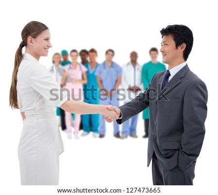 Business people shaking hands with medical staff in background on white background - stock photo