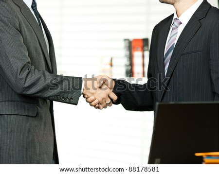 Business people shaking  in office - stock photo