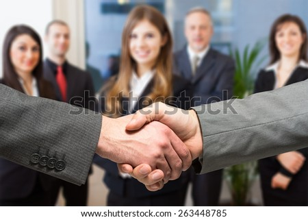 Business people shaking their hands in an office - stock photo