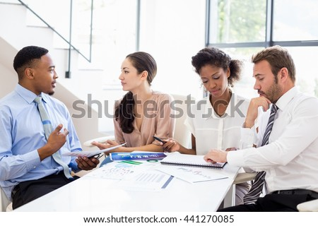 Business people sitting and discussing a report in office - stock photo