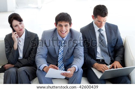 Business people sitting and waiting for a job interview in an office - stock photo