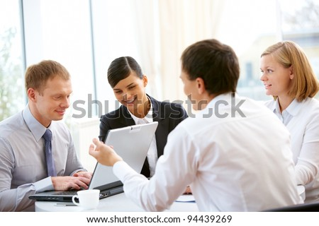 Business people sitting around the table and working together - stock photo