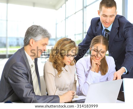 Business people sitting at a corporate meeting working in laptop - stock photo