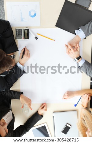 Business people sitting at table with electronic devices on meeting - stock photo