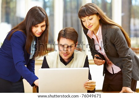 Business people sitting at the table and looking at laptop - stock photo