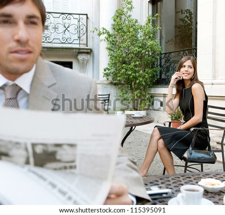 Business people sitting in a classic coffee shop terrace using technology and reading the newspaper, outdoors. - stock photo