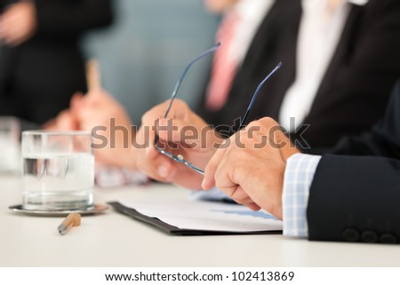 Business - people sitting in a meeting, close-up on hands and man in the front - stock photo