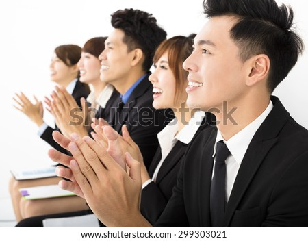 Business people sitting in a row and applauding - stock photo