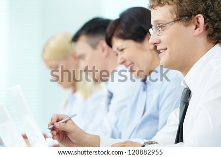 Business people sitting in a row and working, focus on successful young man - stock photo