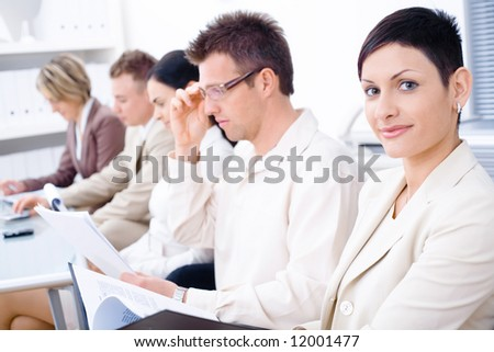Business people sitting in a row and writing notes. Browse my portfolio for vertical version. - stock photo