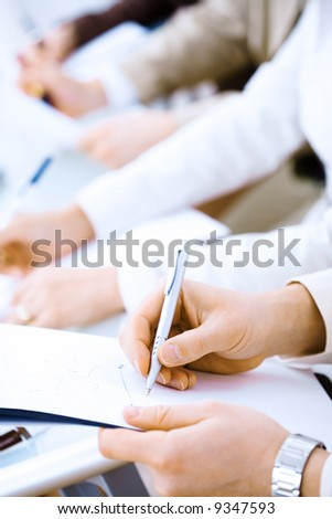Business people sitting in a row and writing notes. Close-up of writing hands. Browse my portfolio for horizontal version. - stock photo