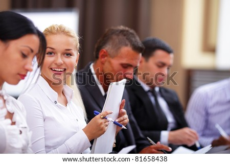 Business people sitting in a row at meeting and making notes. Focus on woman - stock photo