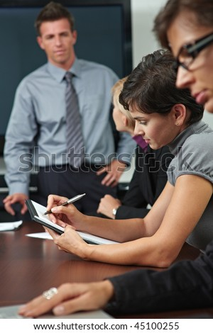 Business people sitting in a row on business training, Focus on woman in middle writing notes. - stock photo