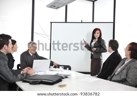 Business people sitting on presentation at office. Businesswoman presenting on whiteboard.