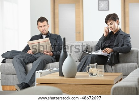 Business people sitting on sofa at office anteroom waiting. - stock photo