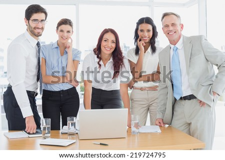 Business people smiling at camera in office - stock photo