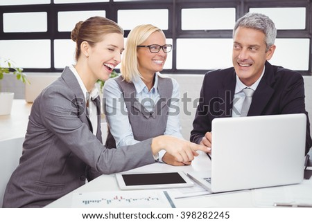 Business people smiling while discussing over laptop at desk in office