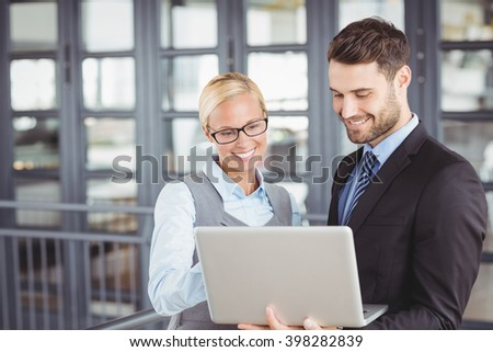 Business people smiling while looking at laptop in office - stock photo
