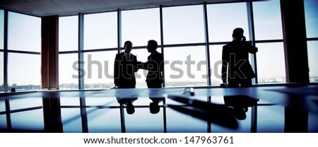Business people spending a usual busy day in office, only silhouettes being recognizable - stock photo