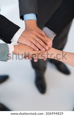 Business people stacking their hands as a symbol of joined efforts - stock photo