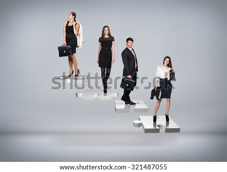 Business people stand on puzzle stairs on the gray background