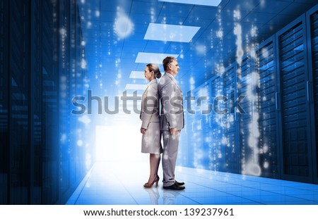 Business people standing back to back in data center with glowing matirx raining down