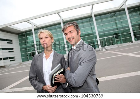 Business people standing in front of exhibition building - stock photo