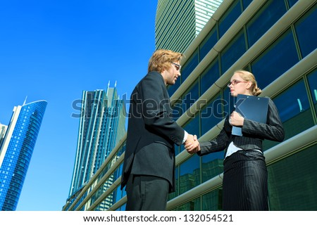 Business people standing in the city and shaking their hands. - stock photo