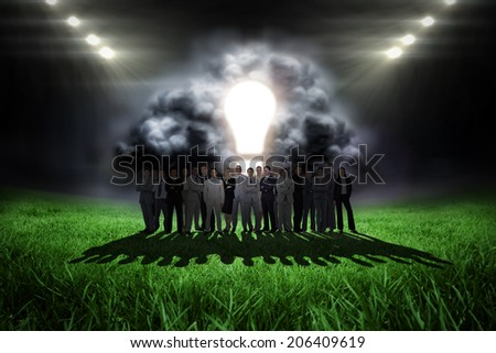 Business people standing up against football pitch with bright lights - stock photo