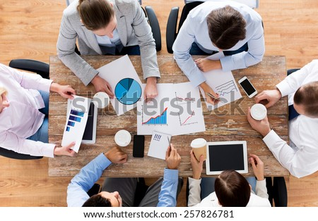 business, people, statistics and team work concept - close up of creative team with charts and gadgets meeting and drinking coffee in office - stock photo