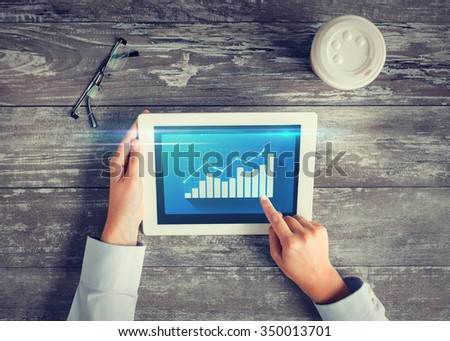 business, people, statistics and technology concept - close up of hands pointing finger to tablet pc computer screen with virtual graph, coffee cup and eyeglasses on table - stock photo