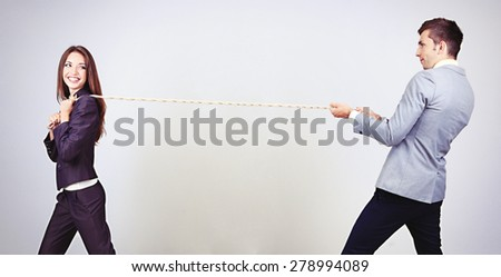 Business people stretching rope on grey background - stock photo