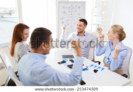 business, people, success and technology concept - smiling business team with tablet pc computers, papers and smartphones showing triumph gesture in office - stock photo