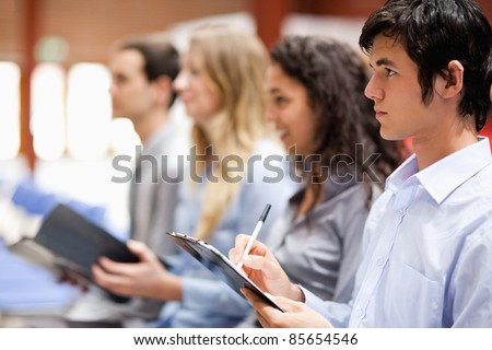 Business people taking notes during a presentation - stock photo