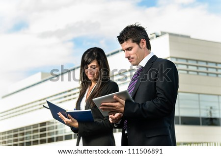 Business people taking notes on tablet and notebook outside of company building. Couple working. Copy space. - stock photo