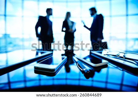 Business people talking at the far side of office - stock photo