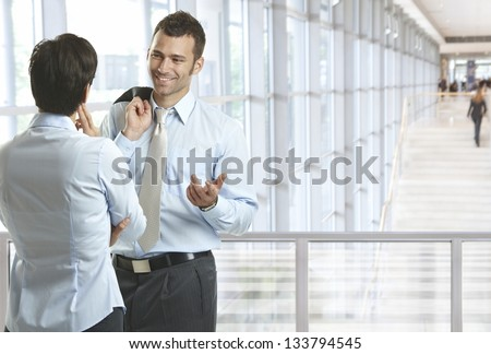Business people talking in office lobby, smiling. Plenty of copyspace. - stock photo