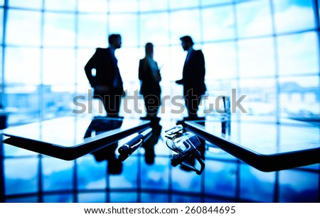 Business people talking in the background and their belongings in the foreground - stock photo