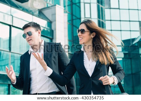 Business people talking, modern office building in the background - stock photo